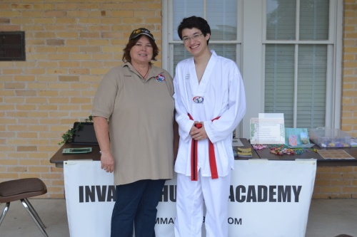 Dr. Linda Brown and Commander Ben in front of the Invasive Hunter Academy at Camp Mabry